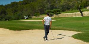 Golfeur touchant le sable dans un bunker